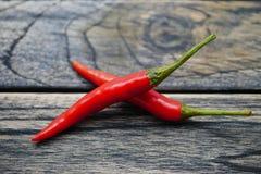 Czerwony bird& x27; s oka chili pieprz odizolowywający na drewnianym tle Zdjęcie Stock