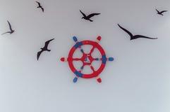Czerwony błękitny ship& x27; s kierownica i latający ptaki - ilustracja na ścianie Obrazy Stock