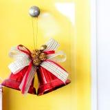Czerwony boże narodzenie dzwonu obwieszenie na kolor żółty ścianie zdjęcie stock