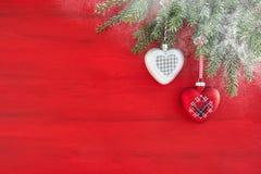 Czerwony Bożenarodzeniowy tło z jedlinowymi gałąź, sercem i śniegiem, kopia obraz royalty free