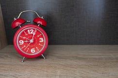Czerwony budzik na drewnie sto?owym i br?zu tle obraz royalty free