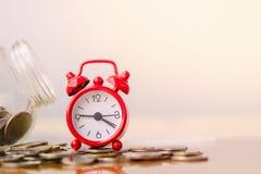 Czerwony budzik na stercie monety w pojęciu lub energia oprócz oszczędzania i pieniądze dorośnięcie Biznesowej inwestyci przyrost zdjęcia royalty free