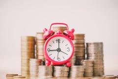 Czerwony budzik na stercie monety w poj?ciu lub energia opr?cz oszcz?dzania i pieni?dze doro?ni?cie obrazy royalty free
