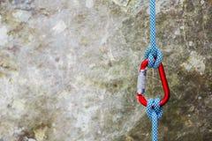 Czerwony carabiner z wspinaczkową arkaną na skalistym tle Zdjęcia Stock
