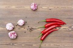 Czerwony chili czosnek z zielonym basilem na drewnianym stole i pieprz fotografia stock