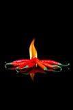 Czerwony chili na czerni powierzchni z płomieniami fotografia stock