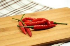 Czerwony chili pieprz na drewnianym ciapanie bloku Zdjęcia Stock
