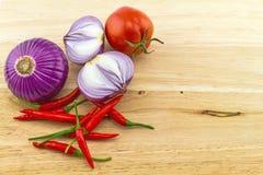 Czerwony chili, pomidor i purpury, pokrajać cebuli na drewnianym Zdjęcie Royalty Free