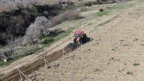 Czerwony ciągnik kultywuje ziemię w winnicy ranku na słonecznym dniu zdjęcie wideo