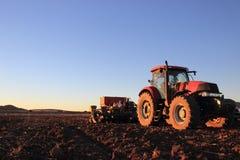 Czerwony ciągnik w otwartym polu z plantatorem fotografia royalty free