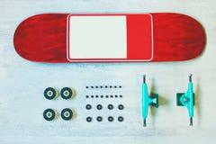 Czerwony deskorolka pokład z innym wyposażeniem na białym drewnianym tle Zdjęcia Stock
