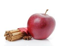 Czerwony dojrzały jabłko i cynamonowi kije zdjęcie royalty free