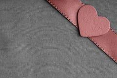 Czerwony drewniany dekoracyjny serce na popielatym szarym sukiennym tle. obraz stock