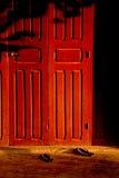 Czerwony drewniany drzwi i kapcie obrazy stock
