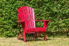 Czerwony drewniany krzesło przeciw zielonemu tłu Obraz Stock