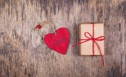 Czerwony drewniany serca i prezenta pudełko na starym drewnianym tle Zdjęcia Stock