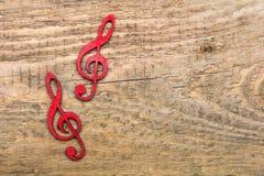 Czerwony drewniany treble clef na drewnianym tle, obraz stock