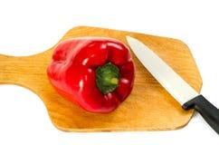 Czerwony dzwon nóż na desce na białym tle Fotografia Stock