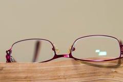 Czerwony eyeglass na starzejący się, pomarańcze książki strona zamknięta w górę makro- strzału zdjęcie royalty free
