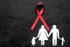 Czerwony faborek dla HIV, pomocy, uzależnienia i anorexia świadomości pobliskiej papierowej sylwetki rodzina na czarnym tło wierz Zdjęcia Royalty Free