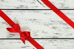 Czerwony faborek z łękiem na białym drewnianym tle Zdjęcia Royalty Free