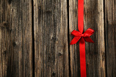 Czerwony faborek z łękiem na brown drewnianym tle Fotografia Stock