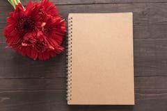 Czerwony gerbera kwitnie i notatnik jest w drewnianym tle Obrazy Royalty Free
