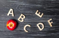 Czerwony jabłko i abecadło robić drewniani listy na ciemnym tle zarząd szkoły 9 jabłczanej duży chłopiec szczęśliwych mienia czer fotografia stock