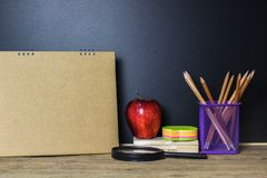 Czerwony jabłko i materiały na drewno stole z Blackboard Obraz Stock