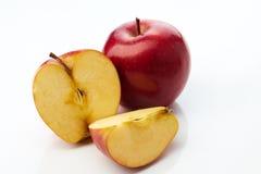 Czerwony jabłko i połówka odizolowywający zdjęcia royalty free