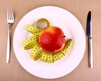 Czerwony jabłko na bielu talerzu z miarą, nożem i rozwidleniem taśmy, Obrazy Royalty Free