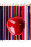 Czerwony jabłko na kolorów ołówkach fotografia royalty free