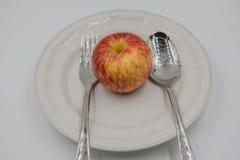 Czerwony jabłko na talerzu i łyżce, rozwidlenie na białym tle Obrazy Stock