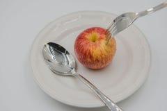 Czerwony jabłko na talerzu i łyżce, rozwidlenie na białym tle Zdjęcia Royalty Free