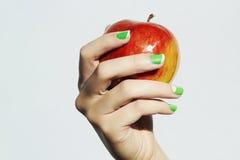 Czerwony jabłko w ręce z manicure'em Żeńskie ręki piękno salonu kobiety gumilaki połysk zdjęcia royalty free