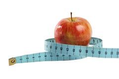 Czerwony jabłko w taśmy miarze odizolowywającej na bielu Fotografia Stock