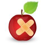 Czerwony jabłko z adhezyjnym bandażem. Zdjęcia Stock