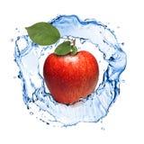 Czerwony jabłko z liśćmi i wody pluśnięciem odizolowywającym Obrazy Stock