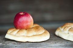 Czerwony jabłko i precel na drewnianym nieociosanym tle Obraz Stock