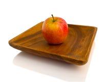 Czerwony jabłko na drewnianym talerzu Zdjęcia Royalty Free