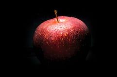 Czerwony jabłko z kroplami na czerni Zdjęcia Stock