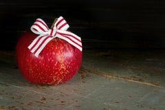 Czerwony jabłko z bożymi narodzeniami ono kłania się na ciemnym tle Obrazy Stock
