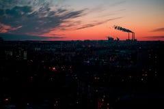 Czerwony jaskrawy żółty purpurowy zmierzch w mieście Przemysłowy centrum, fabryk drymby, piękny niebo z chmurami i dym nad miaste Obraz Stock