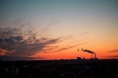Czerwony jaskrawy żółty purpurowy zmierzch w mieście Przemysłowy centrum, fabryk drymby, piękny niebo z chmurami i dym nad miaste Zdjęcia Stock