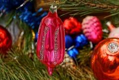 Czerwony jaskrawy nowego roku ` s sopel i nowego roku ` s bawimy się w zielonych igłach obrazy royalty free