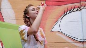 Czerwony kądziołka przędzalnictwo w zwolnionym tempie, wir w ręki dziewczynie outdoors, zakończenie ręki seansu sztuczka z kądzio zdjęcie wideo