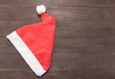 Czerwony kapelusz jest na drewnianym tle z pustą przestrzenią dla Christm Fotografia Stock