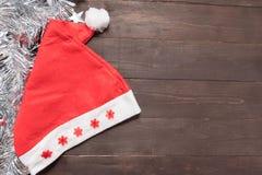 Czerwony kapelusz jest na drewnianym tle z pustą przestrzenią dla Christm Fotografia Royalty Free