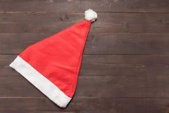 Czerwony kapelusz jest na drewnianym tle z pustą przestrzenią dla Christm Zdjęcie Royalty Free