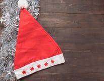 Czerwony kapelusz jest na drewnianym tle z pustą przestrzenią dla Christm Obrazy Royalty Free